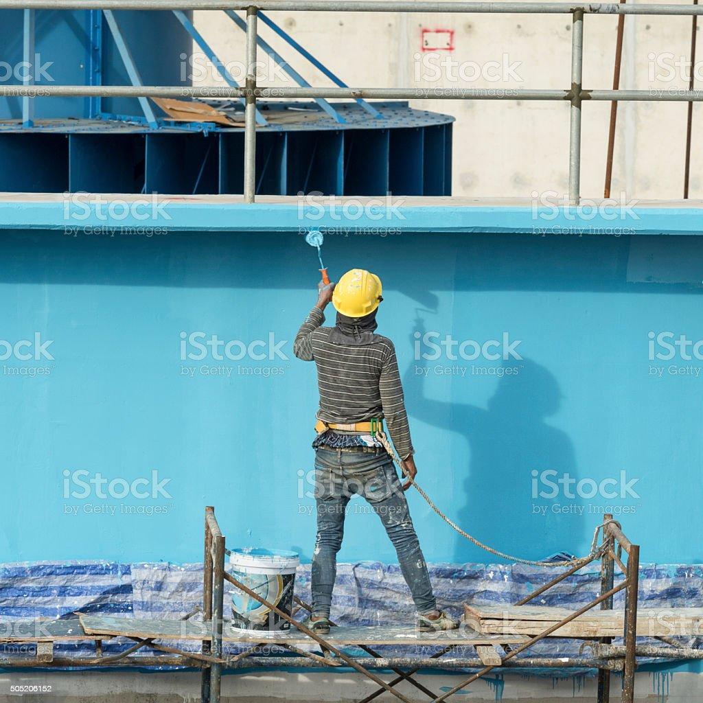 painting facade builder worker 'movement' with roller at Water T stock photo