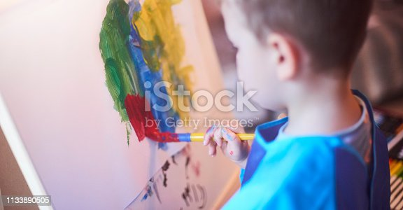 A young boy paints at his easel in preschool or at home