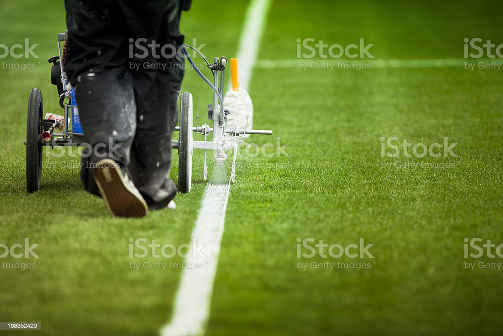 Painting grass turf lines on a sports field royalty-free stock photo