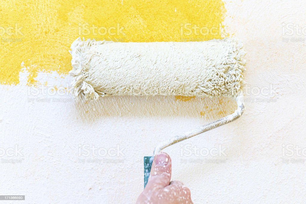 painting hand with paintbrush yellow and white stock photo