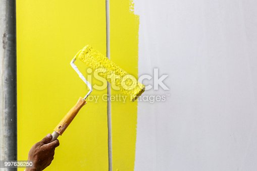 589454570 istock photo Painting hand with paintbrush yellow and white 997636250