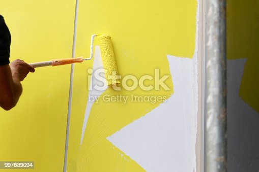 589454570 istock photo Painting hand with paintbrush yellow and white 997639094