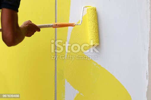 589454570 istock photo Painting hand with paintbrush yellow and white 997639456