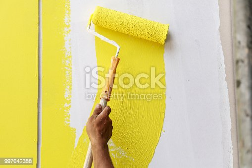 589454570 istock photo Painting hand with paintbrush yellow and white 997642388
