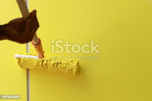 589454570 istock photo Painting hand with paintbrush yellow 997643056