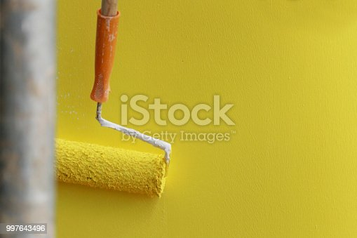589454570 istock photo Painting hand with paintbrush yellow 997643496