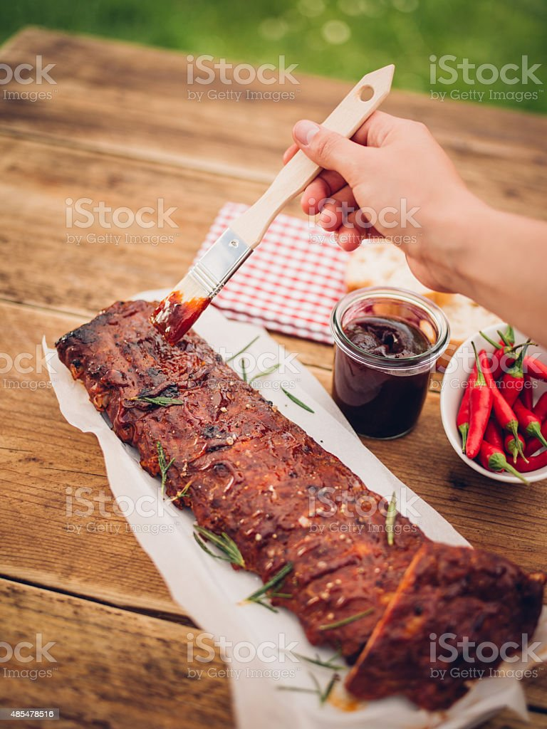 Painting marinade onto rack of ribs with a cooking utensil stock photo