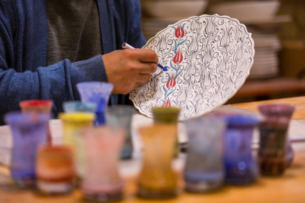 Painting on porcelain. Man painting Turkish tiles on ceramic. stock photo