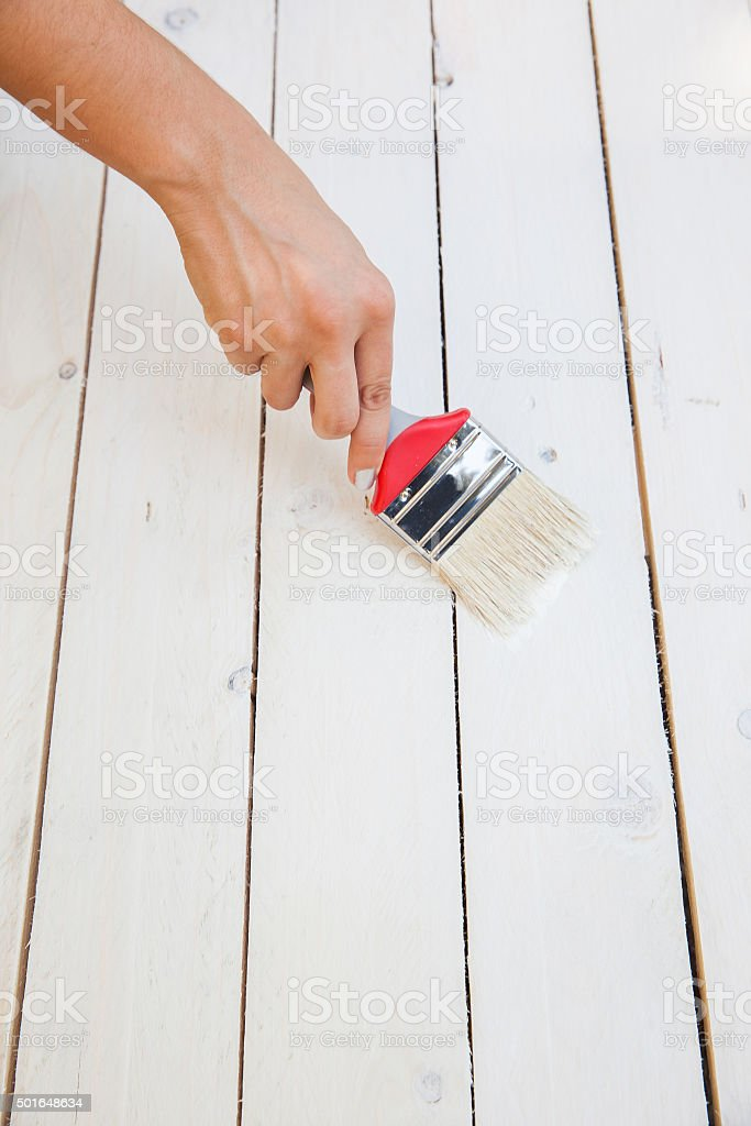 Painting on the wooden furniture with brush in hand stock photo