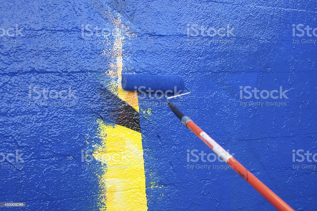 Painting over graffiti with a roller stock photo