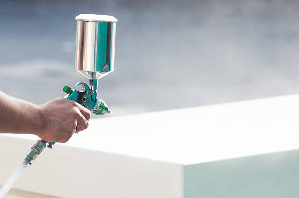 Painting Hand holding a spray gun and painting furniture in furniture factory. airbrush stock pictures, royalty-free photos & images