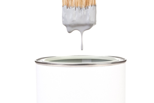 Grey paint dropping from brush into can isolated on white background. DIY creativity concept.