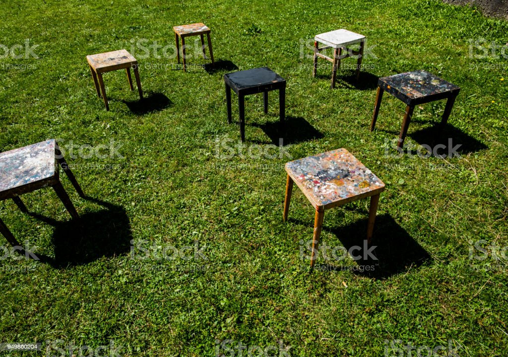 painting tables in a circle on lush green grass stock photo