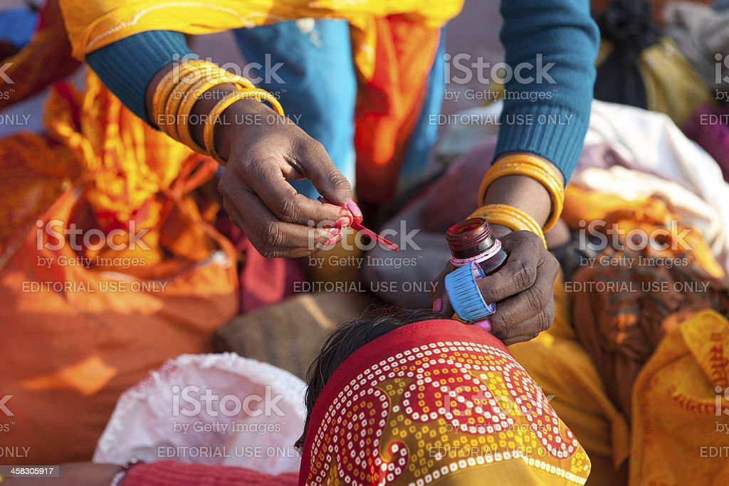 Painting the bindi on woman's face after bath in Ganges royalty-free stock photo