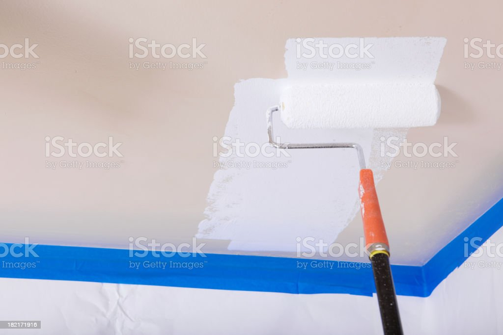 painting the ceiling with a roller stock photo