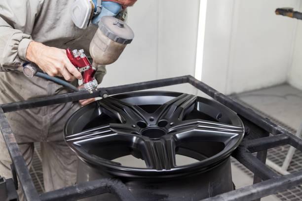 在工業專業車庫的油漆工修理工手中,用黑色的航空器説明繪製汽車元素體 - 鋁合金車輪。汽車服務業。圖像檔