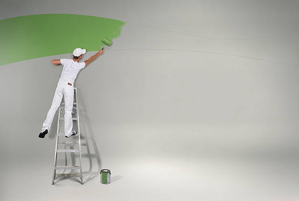 painting the wall green again - painter stock photos and pictures