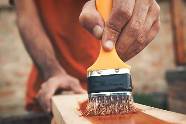 painting the wooden board close up shot - houtbeits stockfoto's en -beelden