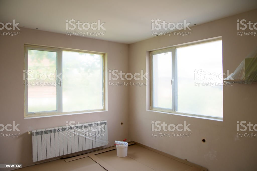 Painting walls in room with roller and ladder during renovation . The...