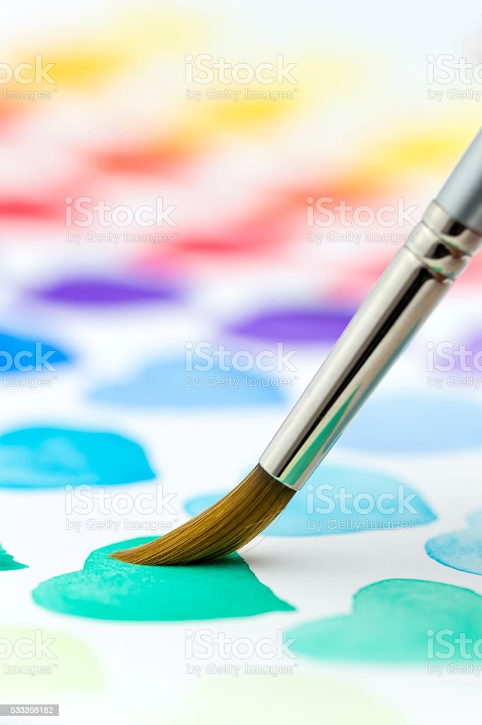 Painting watercolor hearts with a paintbrush. Shallow depth of field. stock photo
