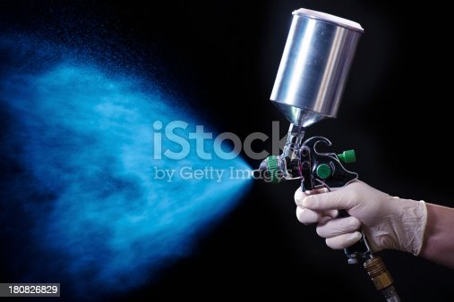 Painter painting with spray gun. Dark background.Similar images: