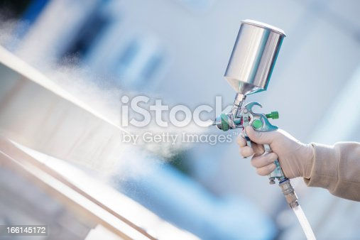 Hand holding a spray gun and painting wood in furniture factory.