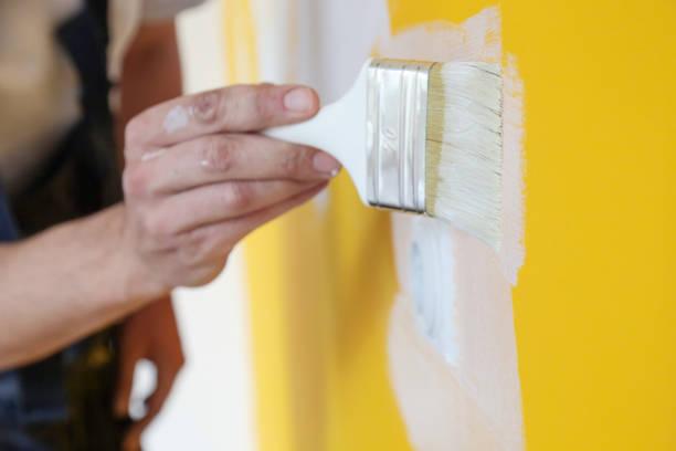 Malerei mit weißer Farbe über einer gelben Wand – Foto