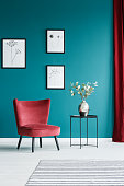 Paintings on the green wall, red armchair, black side table with a flower vase on top