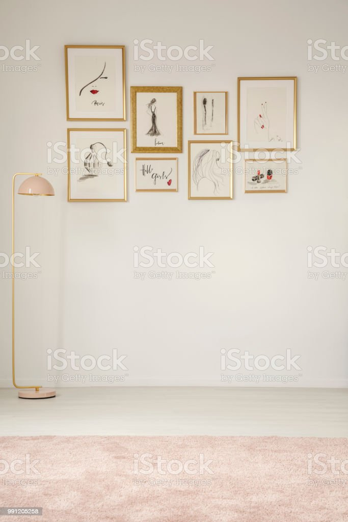 Paintings in golden frames on the white wall, pastel lamp and carpet...