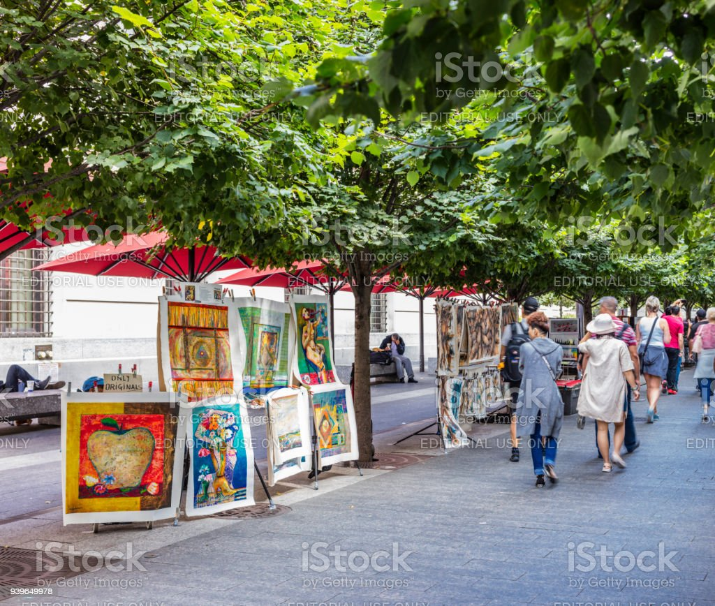 Paintings on sale on Fifth Avenue, near the Metropolitan Museum of Art, and people walking stock photo