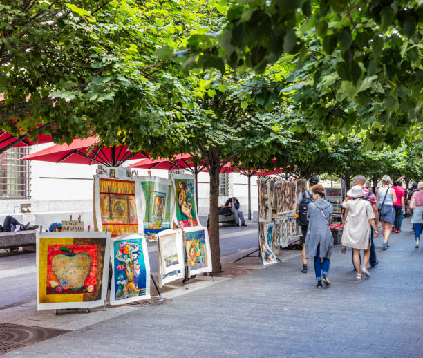 Paintings on sale on Fifth Avenue, near the Metropolitan Museum of Art, and people walking - foto stock