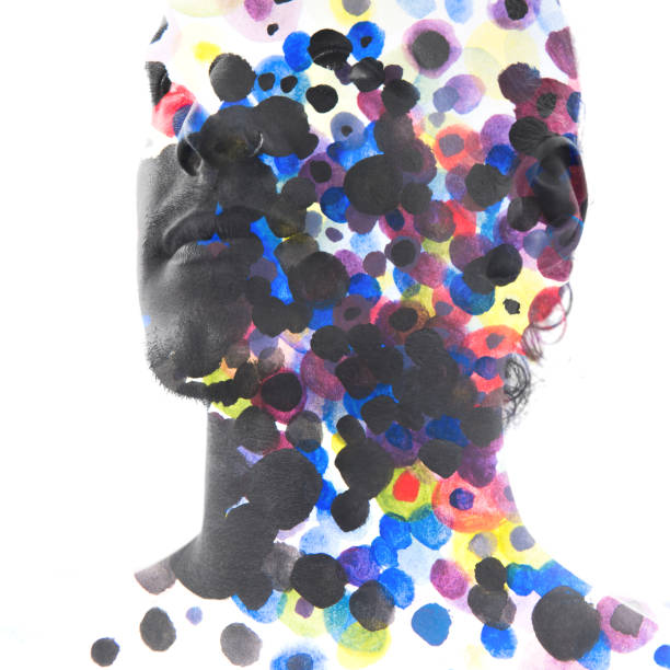 Paintography. Close up of man with strong features and flawless skin dissolving behind hand painted colorful watercolor dots stock photo