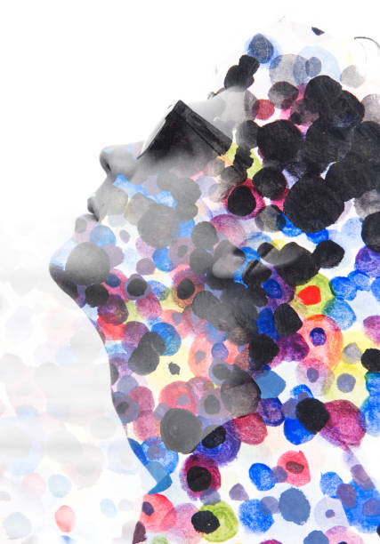 Paintography. Double exposure. Close up of man with glasses and a sad expression dissolving behind hand painted colorful watercolor dots stock photo