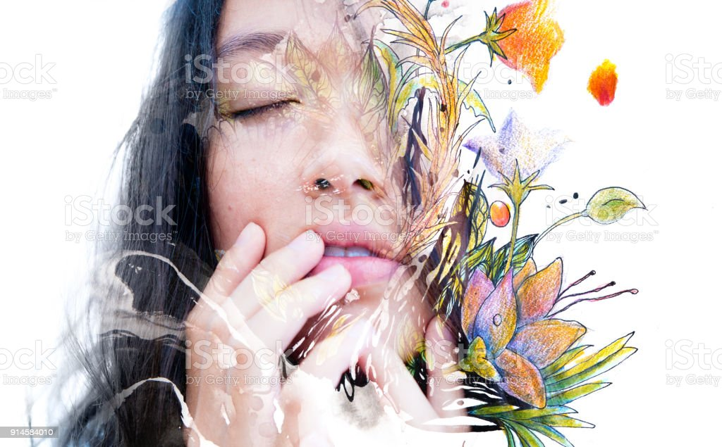 Paintography. Double exposure close-up of a sensual peaceful asian model gently touching her face combined with hand drawn ink and watercolour paintings with floral motifs stock photo