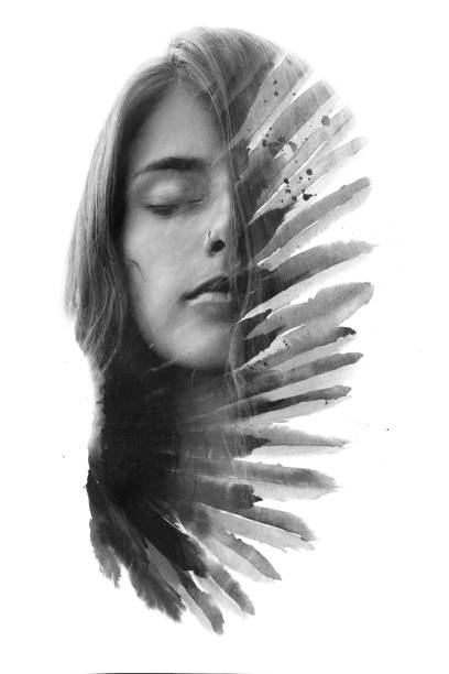 Paintography. Double exposure portrait of a young woman with long flowing hair combined with handmade painting resembling feathers stock photo
