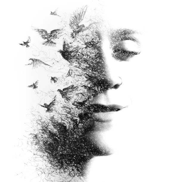 Paintography. Double Exposure portrait of an elegant woman with closed eyes combined with hand made pencil drawing of a flock of birds flying freely resembling disintegrating particles of her being, black and white stock photo