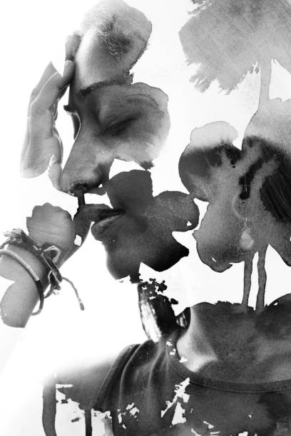 Paintography. Double Exposure profile portrait of a beautiful young woman gently touching her face combined with hand drawn ink painting with floral motifs. black and white stock photo