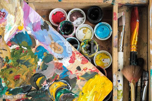 istock Paints of different colors and dirty brushes on the easel of the artist close-up. 1126471371