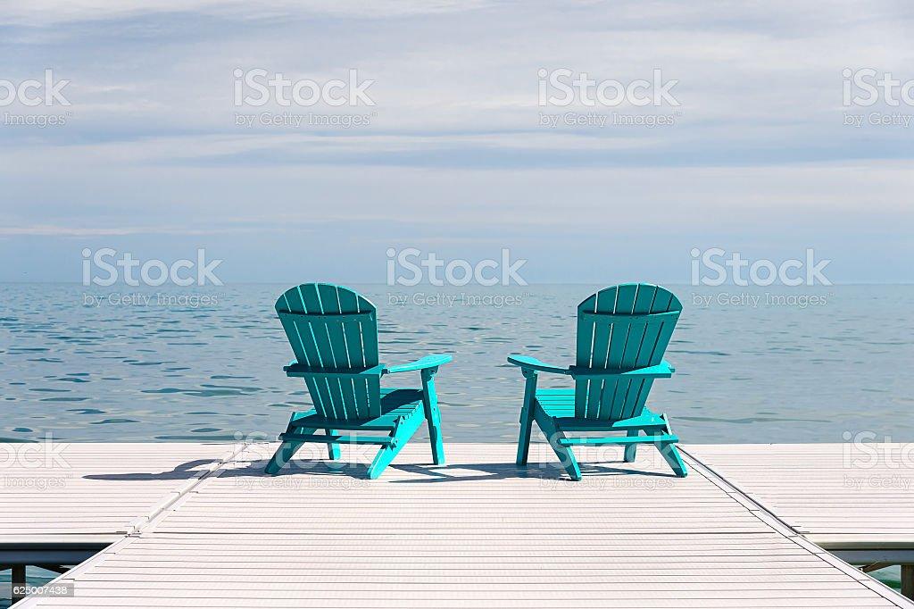 Pair of Adirondack Muskoka Chairs on the Dock stock photo
