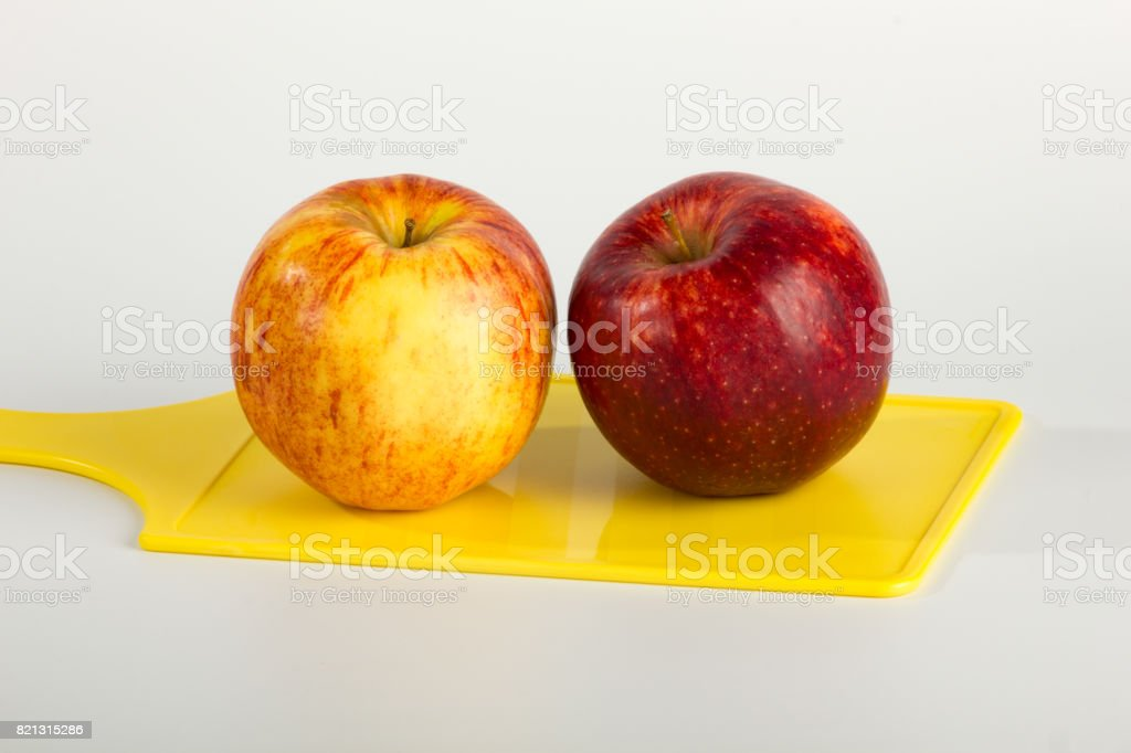 A Pair of Apples on Yellow Cutting Board stock photo