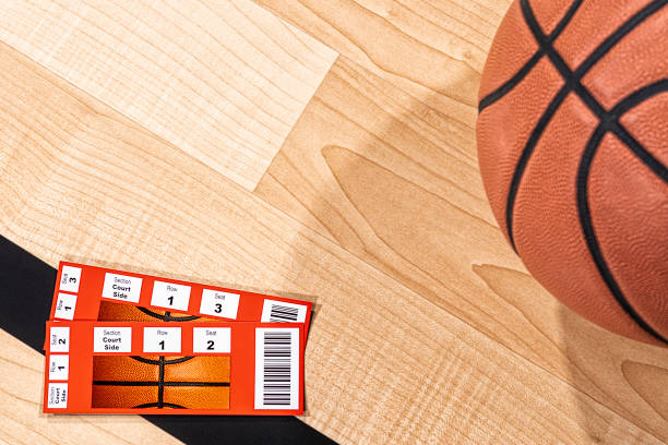 A pair of basketball tickets sitting on the arena wood floor with a basketball