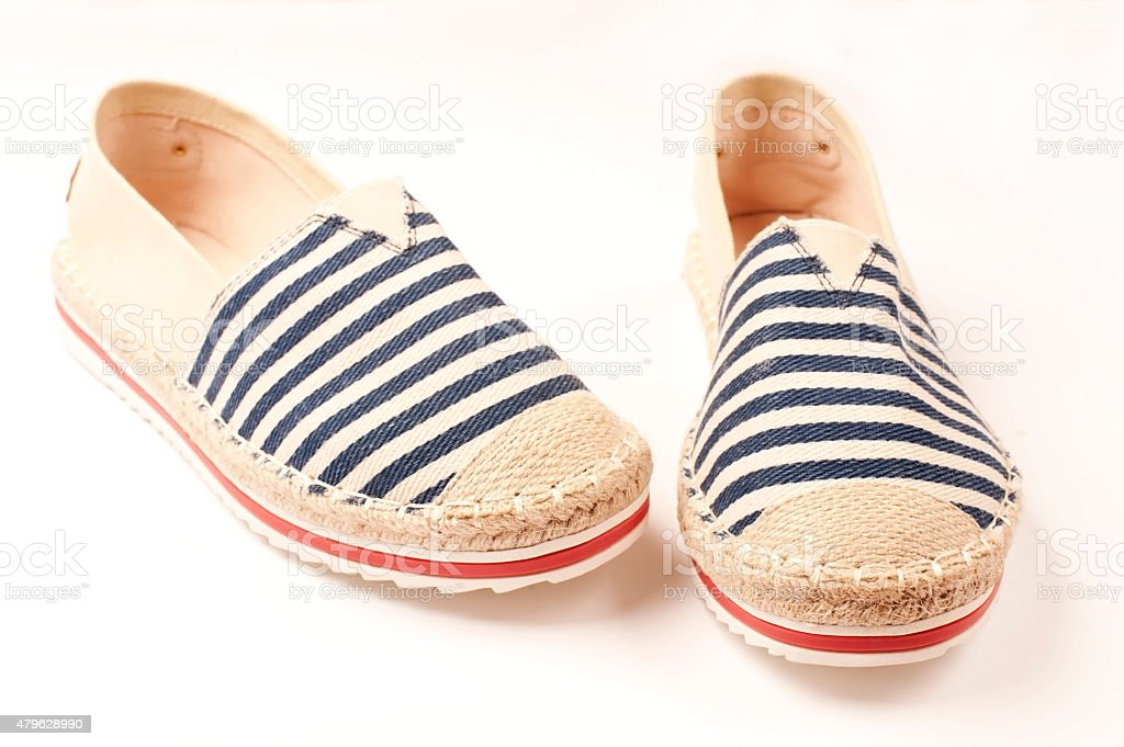 Pair of beige espadrilles with blue and red pattern stock photo