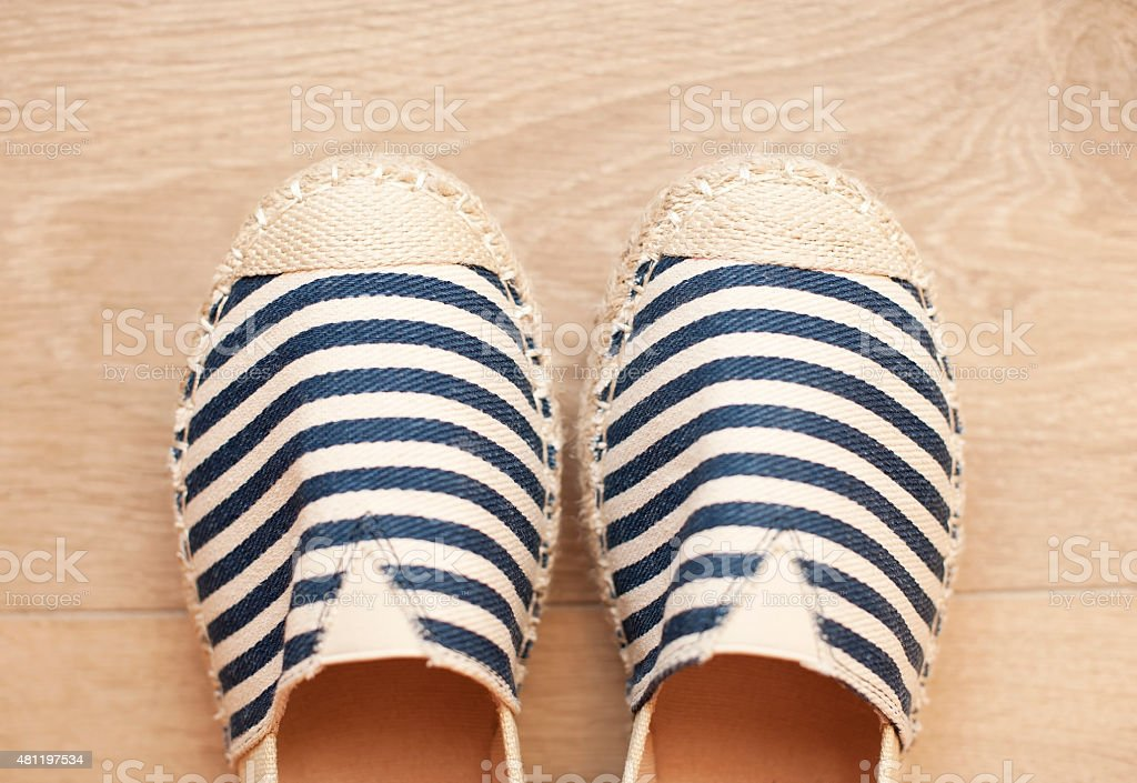 Pair of beige espadrilles with blue pattern stock photo