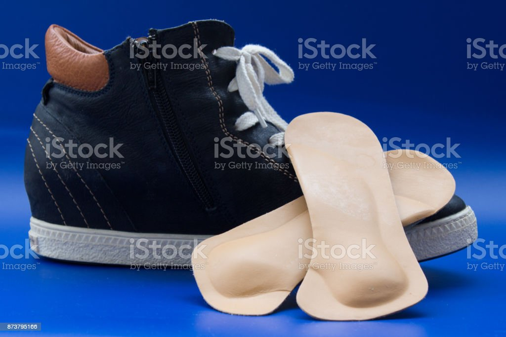 Pair of beige leather orthopedic insoless located on blue boot with white lacing. Blue background. stock photo