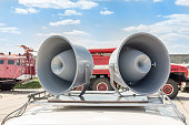 istock Pair of big retro loudspeakers on car roof. Fire trucks on background. Urgent or emergency announcement concept 960636928