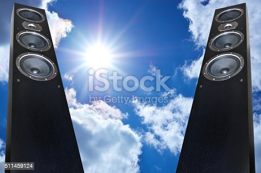 istock Pair of black music speakers on deep blue sky background 511459124