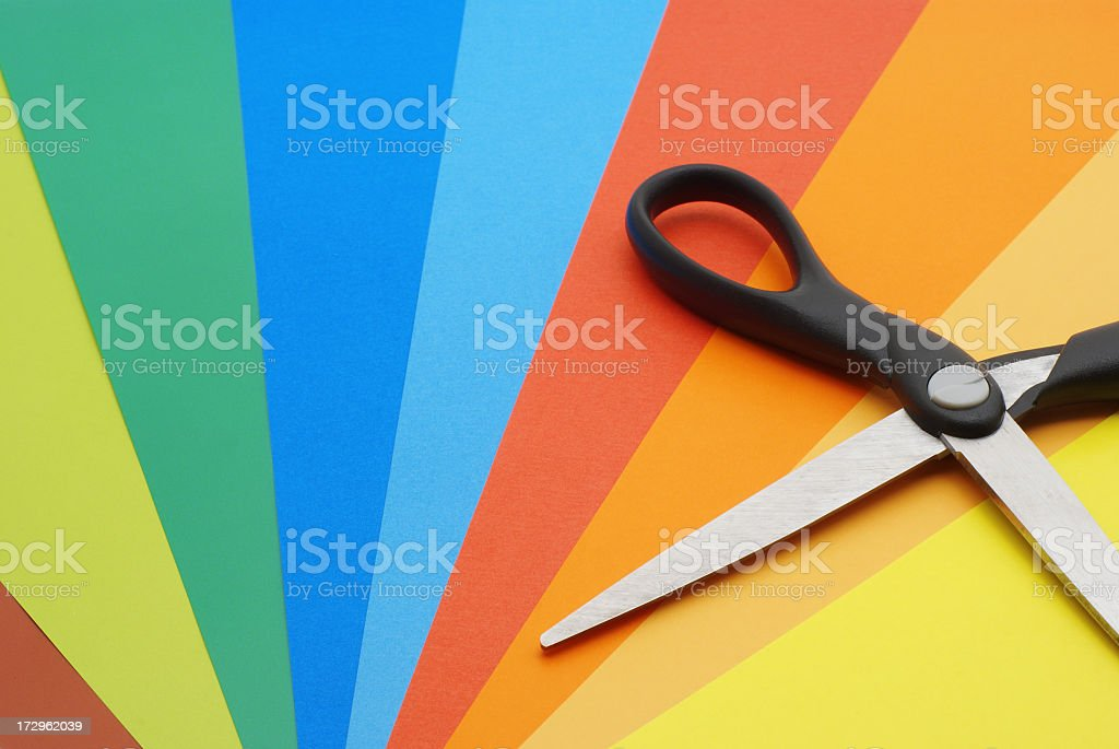 A pair of black scissors on multi-colored paper royalty-free stock photo