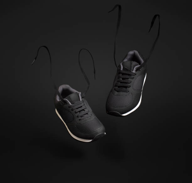 A pair of black unbranded sneakers floating in front of dark background. stock photo