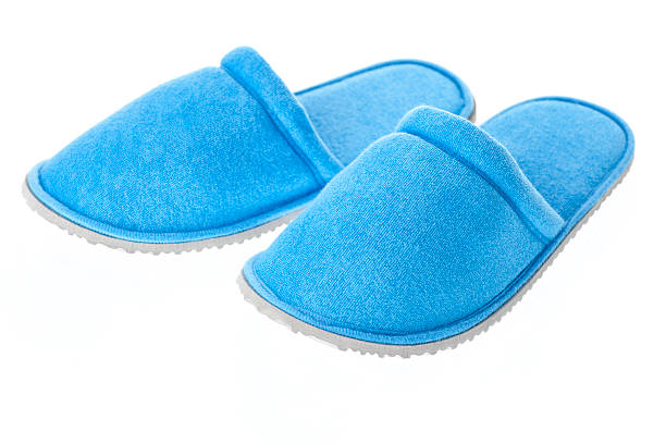 Pair of blue house shoes on white background stock photo