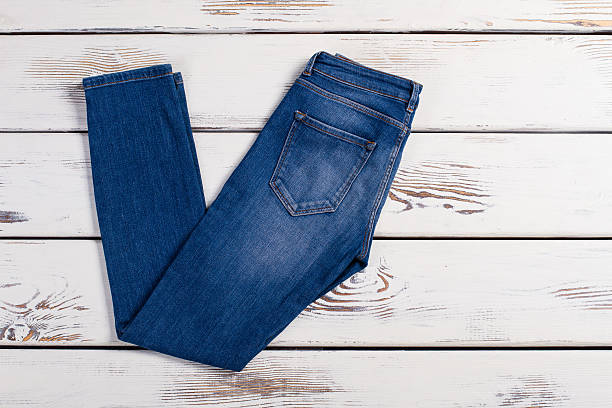 Pair of blue jeans. Pair of blue jeans lay on a white wooden background. skinny jeans stock pictures, royalty-free photos & images